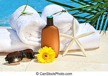White spa towels and tanning lotion by the pool