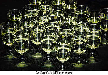 White sparkling wine in glasses on holiday reception table at nightclub.