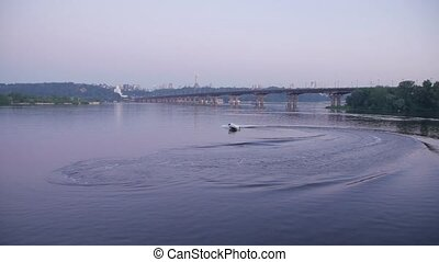 White speed boat floats on the river at sunrise