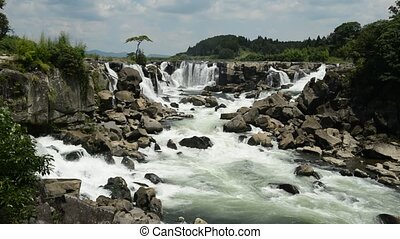 White splashing waterfall falling from several places and ...