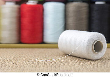 White spools of thread on sackcloth