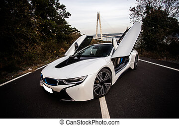 White sport car with black tuning on the forest road, doors open