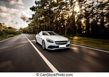 White sport sedan car on the road