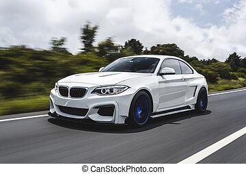 White sport sedan driving on the highway.
