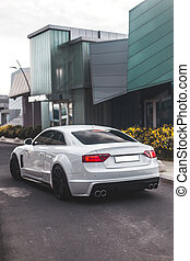 White sport sedan in the commercial zone, view from behind