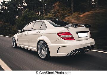 White sport sedan on the road. Backside view