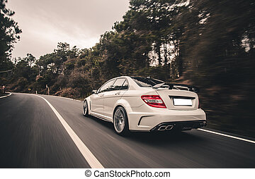 White sport sedan on the road, driving accross the forest