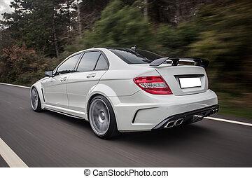 White sport sedan on the road