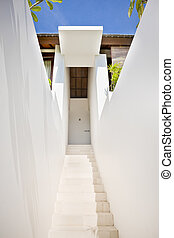 White stairs through the walls to a modern mansion