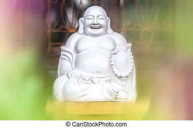 White statue of sitting and laughing fat monk.
