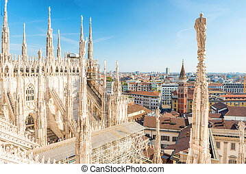White statue on top of Duomo cathedral and view to city of ...