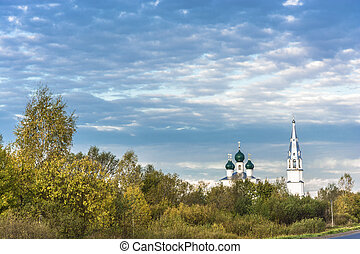 White-stone Orthodox church with green domes against a...