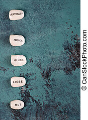 White stone with german words love, trust, courage, luck, fun on a blue textured background, empty space for text