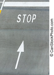 White stop sign painted on tarmac with directional arrow.