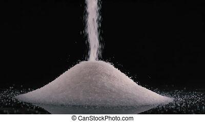 White sugar poured on black background - Pouring white sugar...