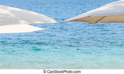white sunshade parasols above azure sea on beach - white...
