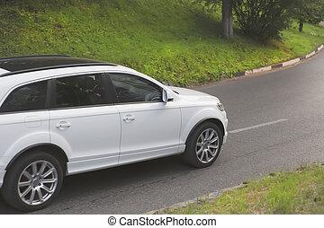 white SUV goes on highway - white SUV goes on twisting...