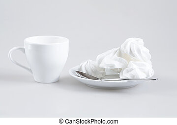 White sweet confectionery on a white saucer and a white cup...