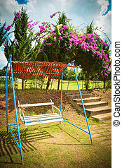 White swing bench for relaxation in the flower garden in summer