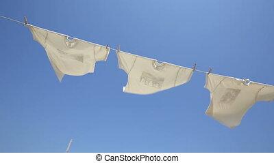 White t-shirts hanging to dry - White t-shirts hanging on...