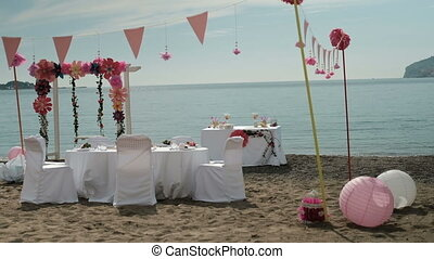 White table chairs floral decorations on beach.