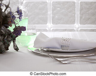 Clean, white table setting with beverage and flower arrangement