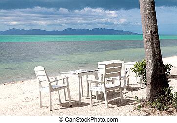 White table set on sand beach facing the ocean
