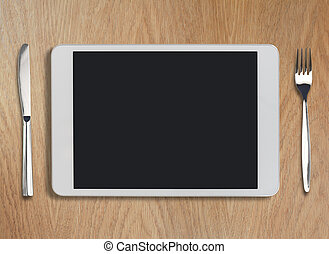 tablet pc on wooden table with fork and knife