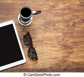 White tablet with black blank screen, glasses and cup of coffee on wood table. Copy space.