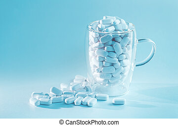 White tablets falling out of mug, drugs and medicine