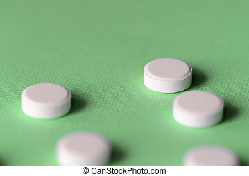 White tablets scattered on a green background close up