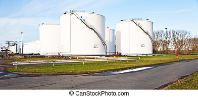 white tanks for petrol and oil in tank farm with blue sky