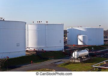 white tanks in tank farm with blue sky - white tanks in tank...