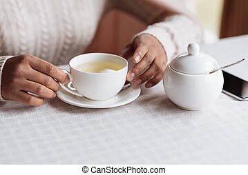 White teacup in the hands of African American man