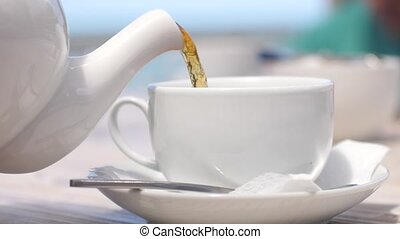 White teapot pouring tea into cup in slow motion in beach...