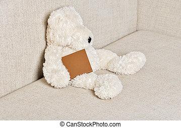 Teddy bear is sitting on the sofa