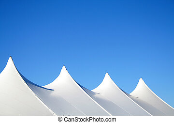 White Tent Tops - White canvas event tents against blue sky.