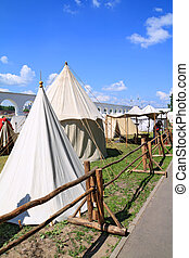 white tents near ancient wall