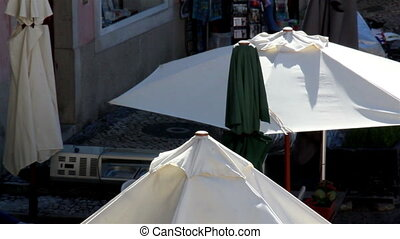 White tents on a hot day setting up of big umbrellas