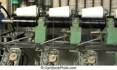 White thread spools at automatic rewinding machine - Big...