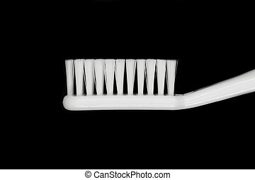 White toothbrush isolated on black background