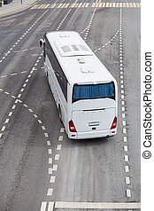 White tourist bus at the intersection of the multi-lane...