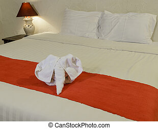White towel in form of elephant on bed