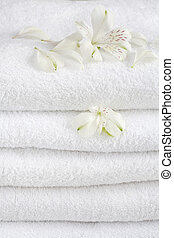 White towels decorated with white flowers for wellness