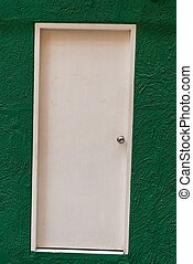 White traditional wooden door on a green wall