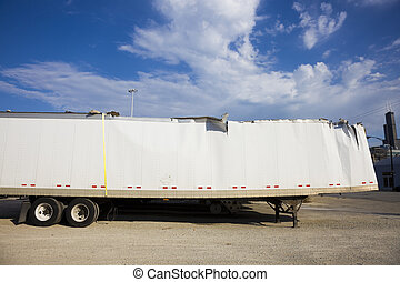 White trailer after accident against blue sky.