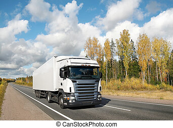 white truck on autumn country highway under blue sky
