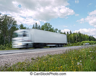 white truck speeding on rural highway, motion blur