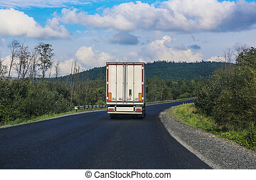 white truck transports freight on  country highway