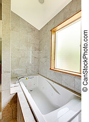 White tub with large window and tiles.